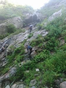 写真上部のハング下が2段15m滝の下段。クラックにジャミングして登る。ぬめりが強く、シャワーを浴びる。